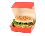 A hamburger sitting in a paper take-out box