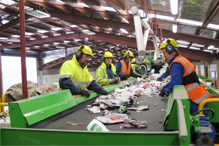 Staff at Southland disAbility Enterprises sorting recycling coming down the conveyor belt